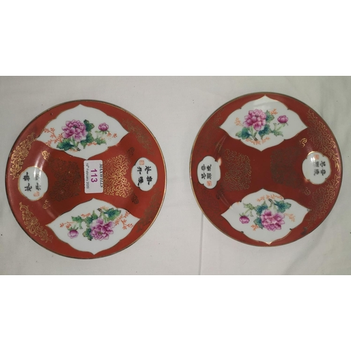 113 - A pair of 20th century Chinese red and gilt plates with hand painted floral decoration, diameter 18c...