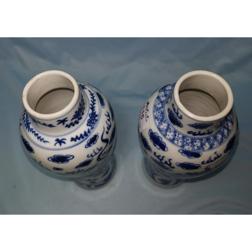 116 - A pair of Chinese blue and white baluster vases decorated with dragons, height 26cm