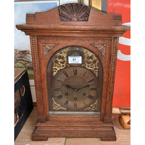 57 - An Edwardian oak mantel clock with brass dial and chiming movement...