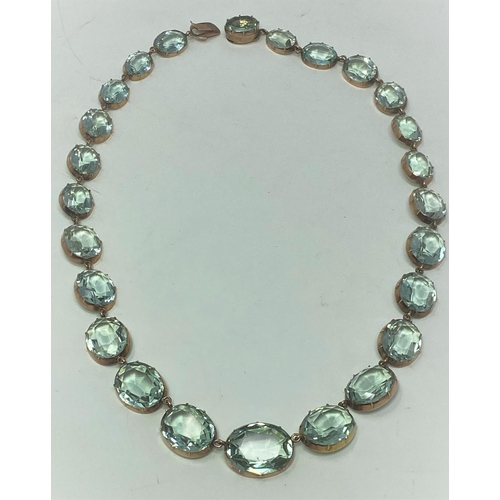 396 - An aquamarine colour faceted stone necklace with yellow metal mounts (tests as 9 carat), 43CM