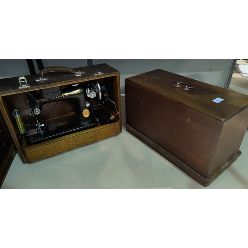 25 - A Singer hand operated sewing mache in leather effect case; a similar by Naumann in inlaid case...