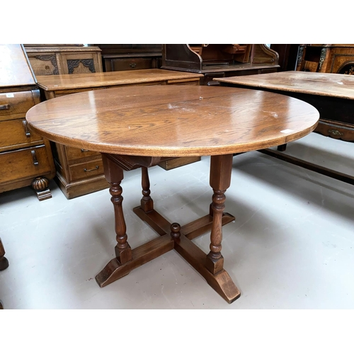 571 - An Oak old charm extending oval dining table with one spare leaf and a set of six (4+2) oak panel ba...