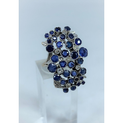 366 - A 1970's lady's modernist multi stone diamond and sapphire ring on white metal shank stamped 18ct an...