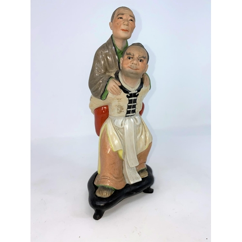 286 - A Chinese ceramic group , son carrying mother on his back (some areas of damage) on wooden stand (a....