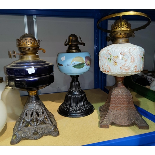 23 - Three Victorian cast iron oil lamps with coloured glass...