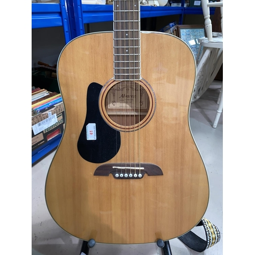 41 - An Alvarez steel strung (strung left handed) acoustic guitar with stand & tuner...
