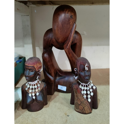 31 - A carved wood figure of 'the thinking man' and a carved pair of African busts...