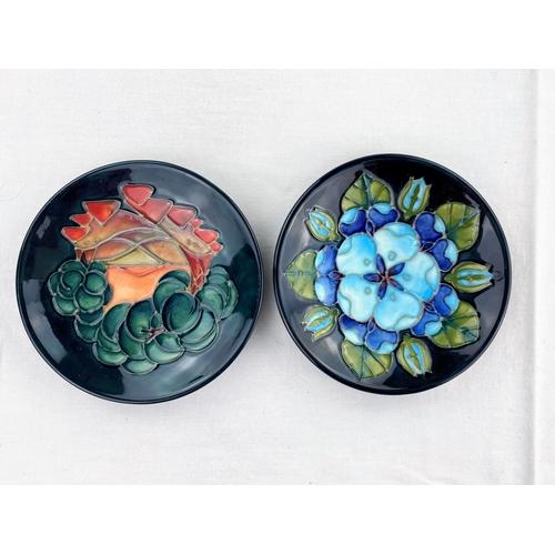 36 - 2 circular Moorcroft pin dishes decorated with blue flowers & leaves, orange flower & fruit respecti...