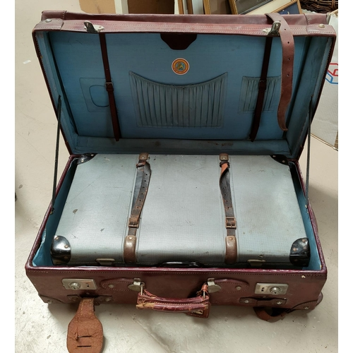 31 - A large strapped leather suitcase; a compressed card suitcase...