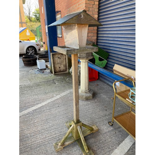 16A - A wooden bird table with slate roof...