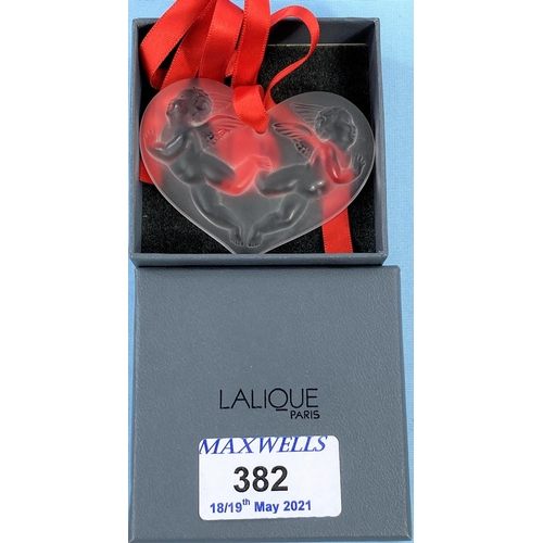 382 - A modern Lalique originally boxed heart, decorated with cherubs in relief, signed Lalique France.