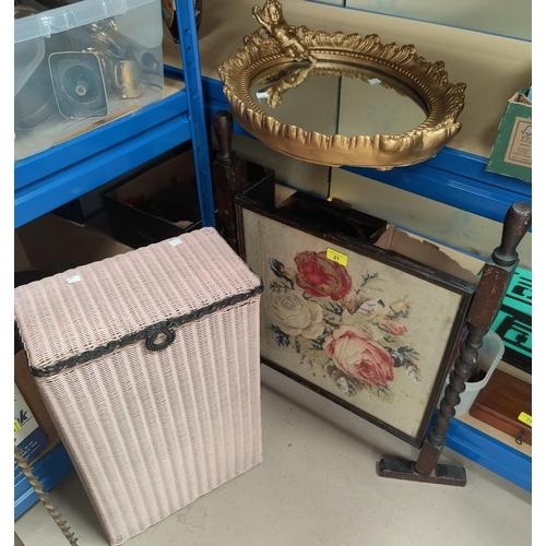 21 - A Lloyd Loom small linen basket; an oak firescreen with tapestry panel; an oval gilt framed mirror...