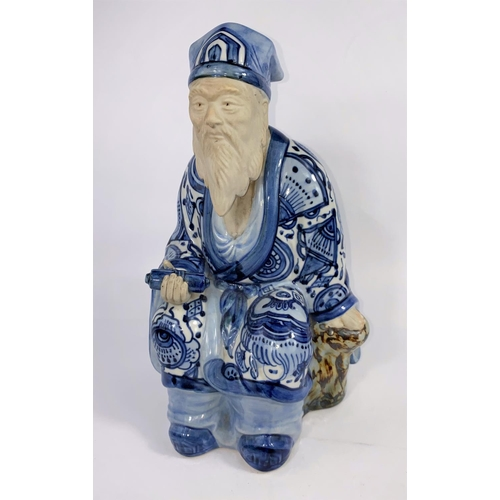 316A - A Japanese blue and white figure of a scholar seated in robes with scroll, ht. 30cm (hand a.f.)(Good...