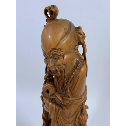 320 - A Chinese carved wood figure of a sage, ht. 24cm (Finely carved rootwood, some cracks notably to fac...