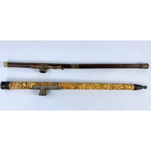 331 - A Chinese brass mounted opium pipe, 48 cm; another in carved bone, 47 cm