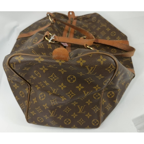 72 - A Louis Vuitton 'sacsouple'/keepall, monogrammed, with tan leather strapping and handles, zip tab em...