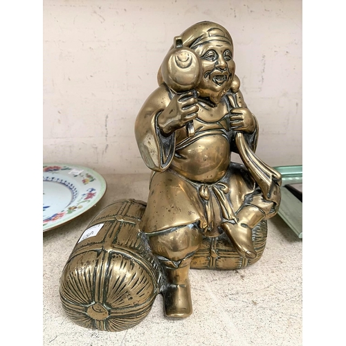 325A - A Japanese polished bronze figure of a sage sitting on bales of hay, ht. 25cm
