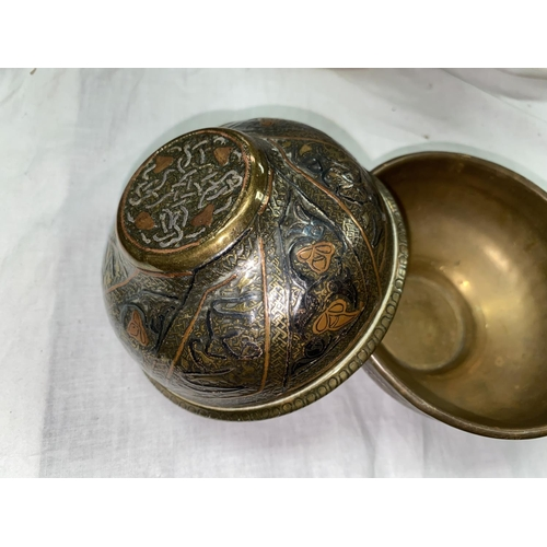 329 - A middle eastern pair of brass bowls decorated with panels of ornamental calligraphy in silver and c...