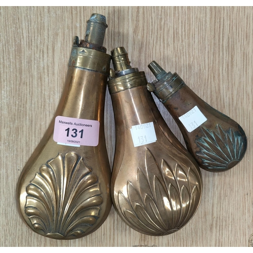 131 - A 19th century brass powder flask, embossed with emion motif, 20cm and 2 similar, 17 & 12cm