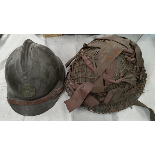 166 - A steel battle helmet with camouflage webbing and a French WWI style helmet