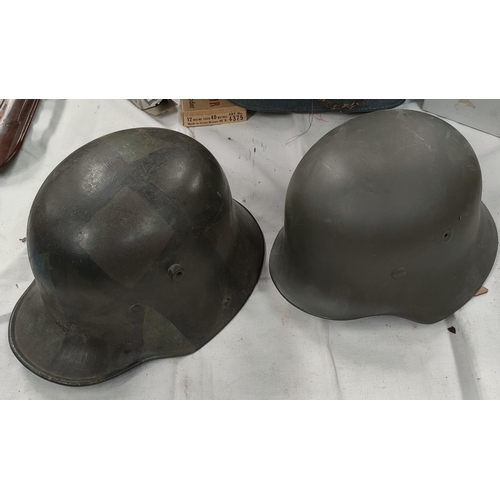 168 - A German style steel helmet with a leather lining and a similar reproduction helmet.