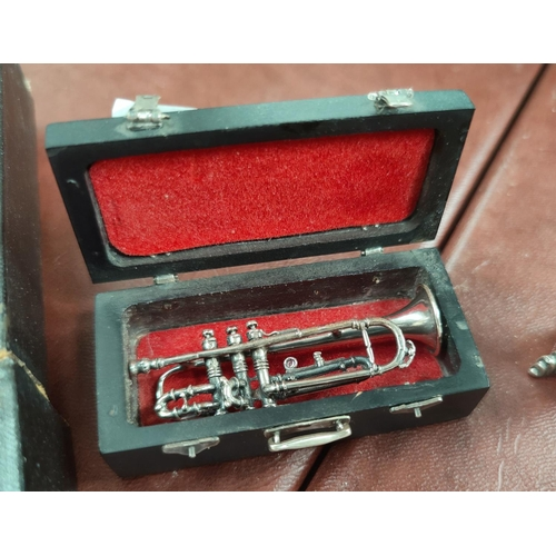 62A - A small selection of silver mounted miniature instruments, violin, Banjo and Trumpet, stamped 925 an...