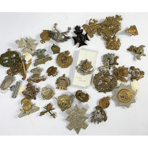 220B - A collection of British Regimental cap badges.