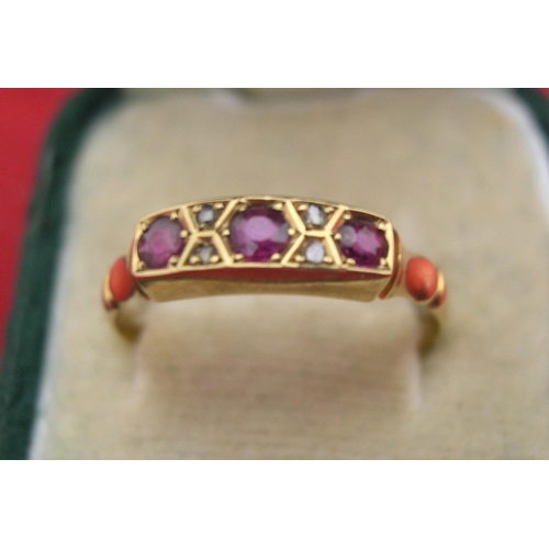 9 - 18ct yellow gold 3 stone ruby ring interspersed with 4 diamond chips,   size S, 1.9 grams gross...