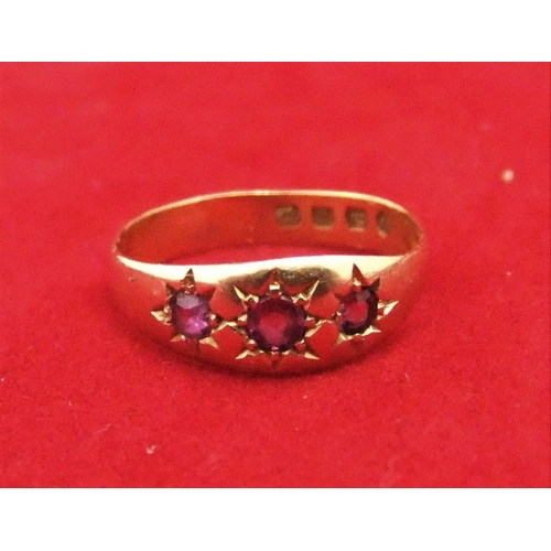 11 - 18ct yellow gold ring with 3 small rubies.  Size K,   2.3 grams gross...