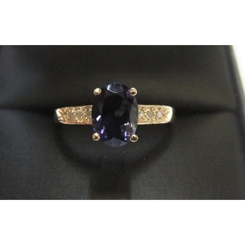 70 - 9ct yellow imported gold ring set with an oval cut iolite and with small diamonds set to the shoulde...