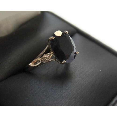 73 - 9ct yellow imported yellow gold ring set with a large black sapphire & with a small diamond set to e...