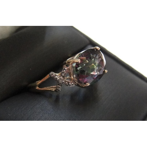 4 - 9ct yellow imported gold ring with a large oval cut mystic topaz with a small diamond to each should...