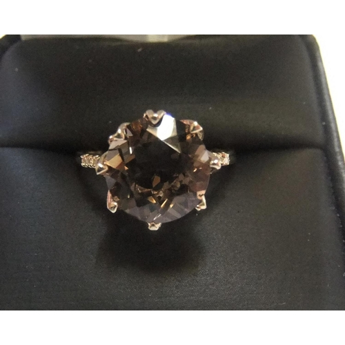11 - 9ct yellow imported gold ring set with a large oval cut smokey topaz and with a small diamond set to...