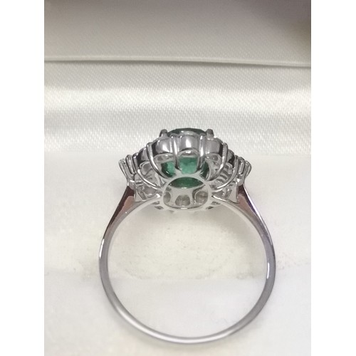 19 - 18ct white gold emerald & diamond ring set with central oval shaped emerald (1.79ct) & a total diamo...