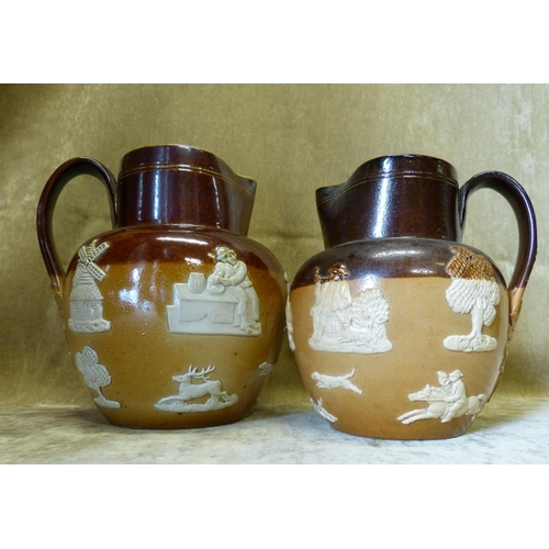 104 - 2 X Royal Doulton Glazed Stoneware Graduated Bulbous Hunting Jugs having raised windmill, animal and...