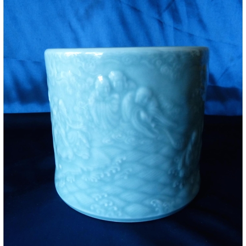 180 - An Oriental Celadon Style Brush Pot having raised figure decoration, 13.5cm high (repair to bottom r...
