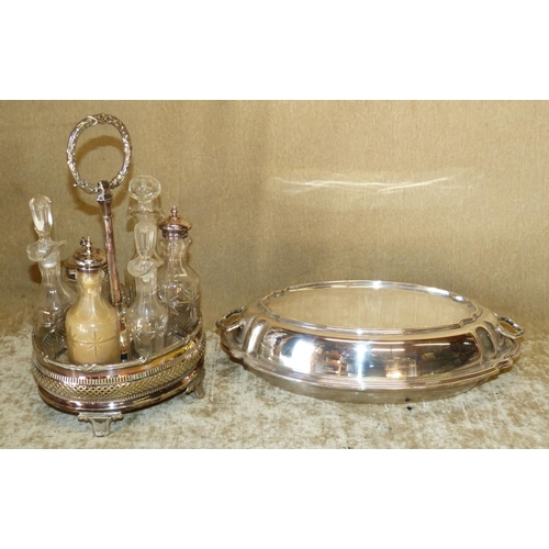 303 - A Silver Plated Oval Cruet Stand having centre carrying handle, set with 6 cut glass bottles on spla...