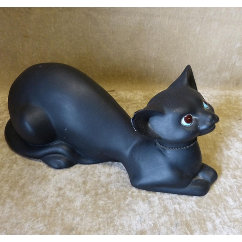 31 - A Modern Pottery Figure of a seated cat on black ground, 32cm long...
