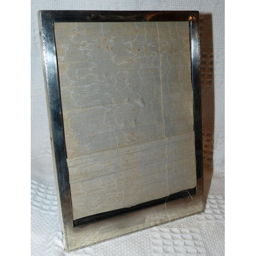331 - A George V Plain Silver Rectangular Freestanding Photograph Frame having chased rim, ebony back stam...