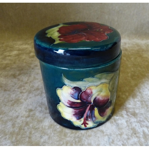 41 - A Moorcroft Round Lidded Pot on green ground with multicoloured floral and leaf decoration, 9.5cm hi...