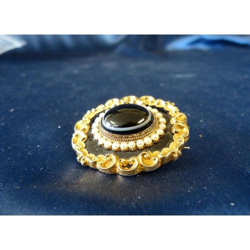 440 - A 19th Century Gold Mourning Brooch set with centre banded agate surrounded by half pearls with scro...