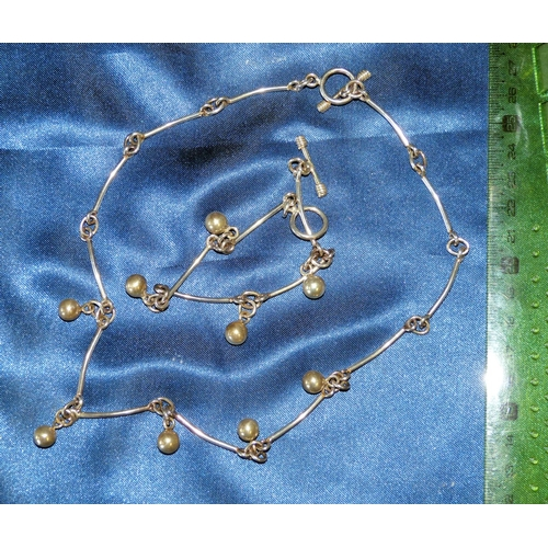 468 - A Silver Necklace having various drops, also a matching bracelet...