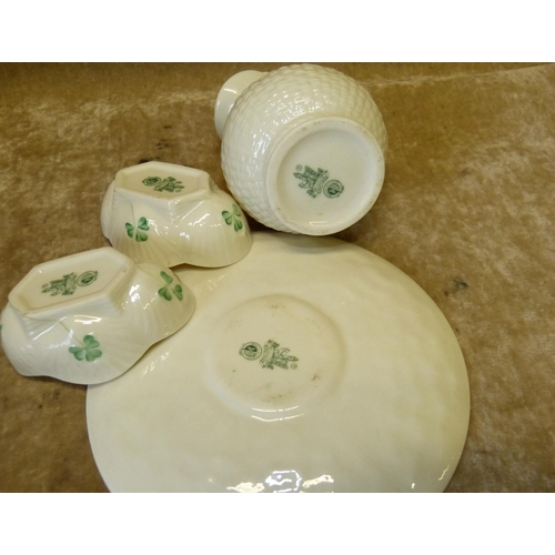 49 - A Belleek Bulbous Shape Jug, a pair of similar Belleek oval salts and a similar saucer (4)...