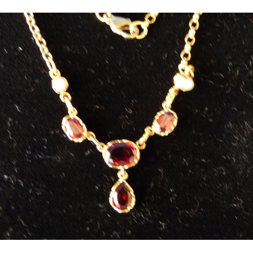 534 - A 9ct Gold Drop Necklace mounted with 4 Garnets and 2 half Pearls, 39cm long...