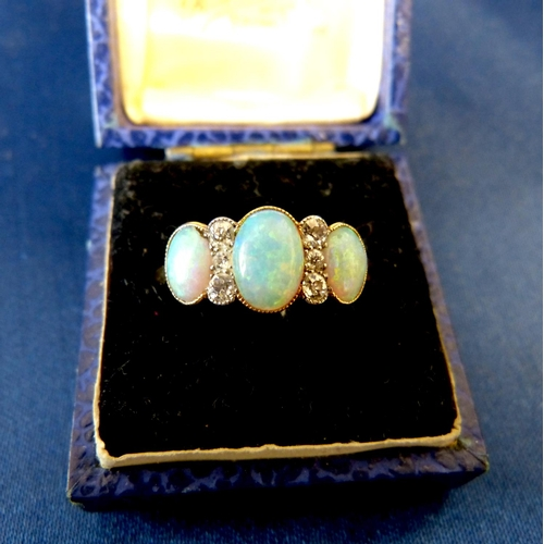 569 - A Gold 3 Stone Opal Ladies Ring interspersed by 2 rows of 3 diamonds...