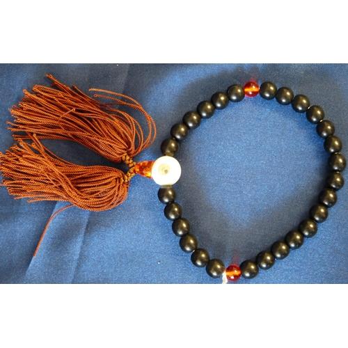 591 - An Oriental Black Bead Bracelet with tassel...