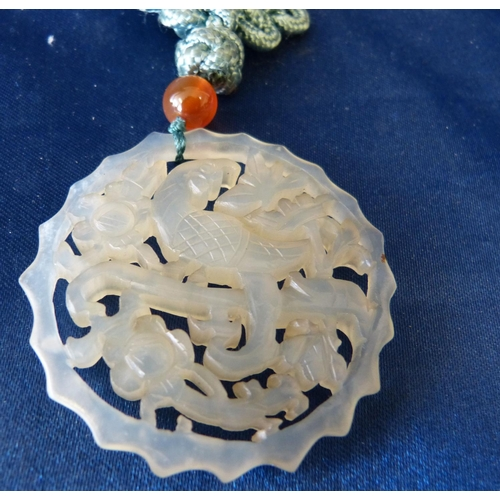 593 - An Oriental Jade Round Pierced Plaque having bird and floral decoration with cord necklace...