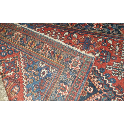 611 - A Persian Carpet on red and blue ground having centre medallion, 2m 5cm, 1m 26cm (worn)...