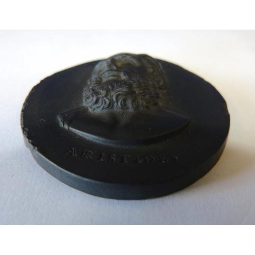 64 - A Wedgwood Basalt Oval Plaque having raised figurehead motif