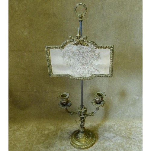 687 - A 19th Century Gilt Metal Double Candlestick with adjustable Face Screen having raised floral, leaf ...